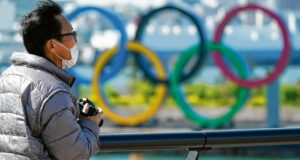A visitor wearing a face mask stands near the Olympic rings at Tokyo'